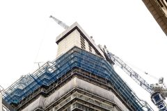 Building Under Construction White Sky. Building with a blue crane undergoing construction with a white sky background Royalty Free Stock Photography