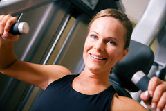 Building body. Beautiful girl doing fitness exercises in a gym stock photography