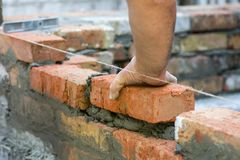Building brick block wall on construction plant. Worker builds a brick wall in the house. Construction worker laying bricks on ext. Erior walls royalty free stock photography