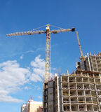 Building A Building. Tower cranes used in construction of a partially completed building stock image