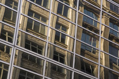 Building in a Building. Reflection of an old building in the windows of a modern building Stock Image