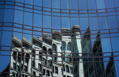 Building on a Building. A shot of many curving windows on a buidling reflecting another building and a clear blue sky Stock Images