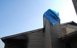 Building burned and boarded up. Apartment building after a fire, boarded up and part of the chimney covered with a blue tarp stock images