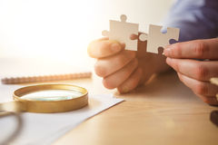 Building a business success. The hands with puzzles Royalty Free Stock Photos