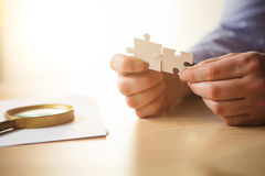 Building a business success. The hands with puzzles Stock Photography