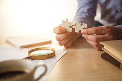 Building a business success. The hands with puzzles Royalty Free Stock Image