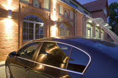 Building and car at night. Old building and car with reflections at night Royalty Free Stock Image