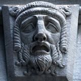 Building carving detail of sad worried expression on face. stock images