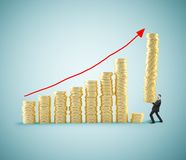 Building chart coins. Businessman with tower of coins building chart coins Royalty Free Stock Image