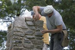 Building Chimney. Masons Building a Stone Chimney Stock Photography