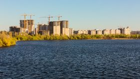 Building of city habitation on bank big river Royalty Free Stock Images