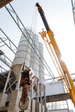 Building clan carrying cargo with a hook on a construction site Royalty Free Stock Images