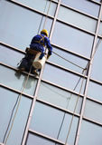 Building Cleaning,Dustman. Dustman cleaning the building wall Royalty Free Stock Photo