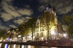 Building with clock in Amsterdam seen from canal at night. Building with a clock in Amsterdam seen from canal at night Royalty Free Stock Photography