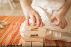 Building collapse games. Child hands playing with wooden blocks the unstable tower. Building collapse games Stock Photos