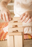 Building collapse games. Child hands playing with wooden blocks the unstable tower. Building collapse games royalty free stock photography