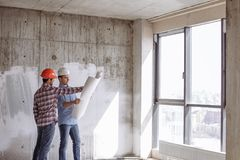 Building company. handsome engineer is showing a construction plan. To the customer in front of the panorama window royalty free stock photography