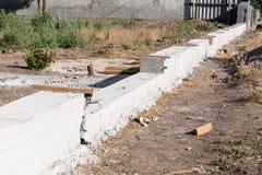 Building concrete foundation for wooden rural fence. Foundation for fence. Building concrete foundation for wooden rural fence royalty free stock image