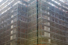 Building construciton under  debris netting , aluminum fence and scaffold Royalty Free Stock Image