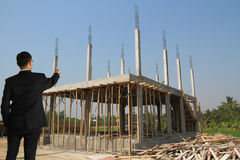 Building construct site. Businessman in building construct area cement pillar and wood Stock Image