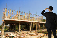 Building construct site. Businessman in building construct area cement pillar and wood Stock Images