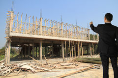 Building construct site. Businessman in building construct area cement pillar and wood Stock Photo