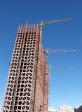 Building construction. Unfinished building construction and cranes Royalty Free Stock Photos