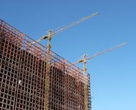 Building construction. Unfinished building construction and cranes Stock Photos