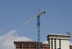 Building Construction. A crane atop a building under construction Stock Image