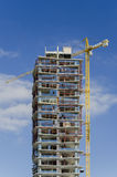 Building Construction. A high rise building construction with a tower crain Royalty Free Stock Image
