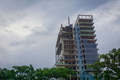 Building construction with cloudy sky as background and surrounding by trees photo taken in Jakarta Indonesia Royalty Free Stock Photography