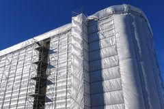 Building construction, the building covered with a grey tarpaulin. Stock Image