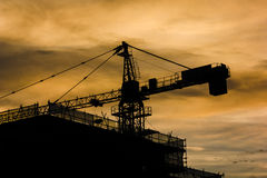 Building and Construction Crane during golden hour bright. This is a picture of a building under construction company. The construction crane can be seen behind Stock Image