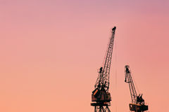 Building construction cranes against red sky Stock Photo