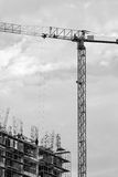 Building in construction and a hoisting crane. Building in construction, hoisting crane at dusk and workers silhouettes black and white royalty free stock photos