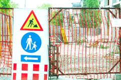 Building construction site gate with warning signs for caution. Royalty Free Stock Photography
