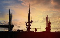 Building construction site in silhouette. Silhouette of workers at building construction site in warm orange-blue twilight stock images