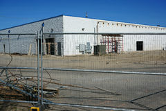 Building in construction site surrounded by iron fence Stock Photography