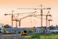 Building construction site with tower crane machinery. Building construction site with tower crane and backhoe machinery in sunset vintage tone color royalty free stock image