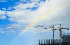 Cranes building construction. Building construction site use two crane background rainbow blue sky with copy space Stock Image