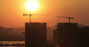 Building construction at sunset timelapse. Timelapse of a construction with cranes at sunset in Kiev 4K stock footage