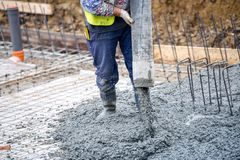 Building construction worker pouring cement or concrete with pump tube. On foundation site royalty free stock photos