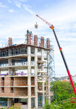 Building and construction workers. Crane and building construction site against blue sky Royalty Free Stock Photo