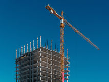 Building construction with a yellow crane on a clear blue sky Stock Images