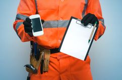 Building contract. Fix list. Call to a repair man. Building contract. Fix list. Builder is holding note pad and mobile phone with blank screen in his hands stock photos