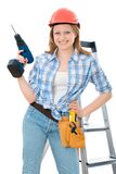 Building contractor. Cute carpenter woman holding a drill, wearing a hardhat Royalty Free Stock Photography