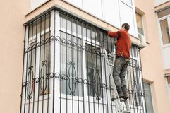 Free Building Contractor Installing Balcony Window Iron Security Bars. Metal Grid For Windows And Balcony. Stock Photography - 121112002
