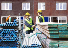 Building contractors. Two building contractors shaking hands behind stacks of scaffolding material, in front of a newly completed residential building complex Stock Images