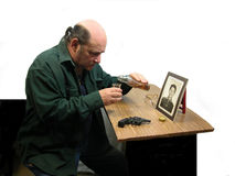 Building Courage. A man building courage by drinking while looking at a photo,with a gun on the table Stock Photography