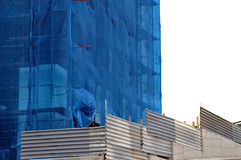 Building covered with construction debris netting. Aluminum fence and scaffold Royalty Free Stock Photo